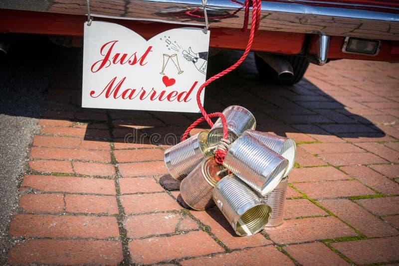 Cans som fästas till baksidan av en bil för att fira en wedd royaltyfria foton