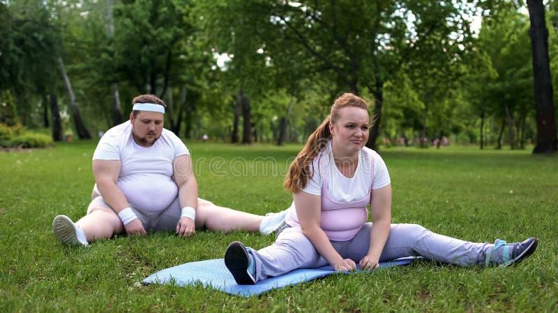 Cansaço de sentimento dos pares gordos após o treinamento da aptidão, maneira dura de perder o peso imagens de stock