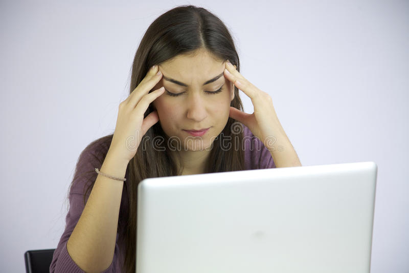 Cansado con dolor de cabeza mientras que trabaja en el ordenador imagenes de archivo