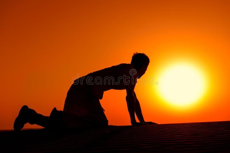 Cansado e enfraqueça o homem em todos os fours no por do sol foto de stock royalty free