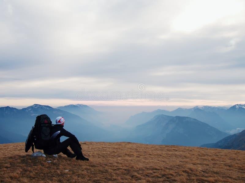Cansado el turista en negro con la mochila se está sentando en piedra en prado y está mirando en el valle brumoso Otoño en montañ fotografía de archivo libre de regalías
