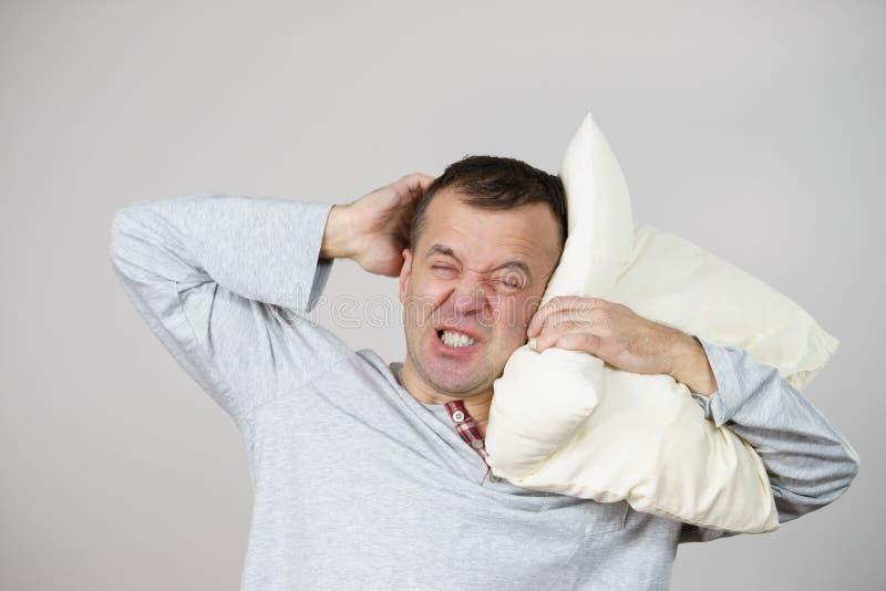Cansado soñoliento del hombre con la almohada en gris fotografía de archivo libre de regalías