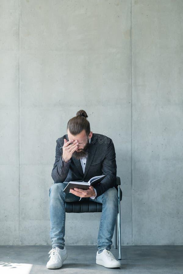 Cansancio de lectura concentrado de la libreta del hombre de negocios foto de archivo libre de regalías
