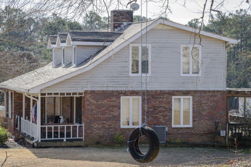 Canse o balanço que pendura ao lado da casa do sul típica em Geórgia, foco no balanço do pneu imagem de stock royalty free