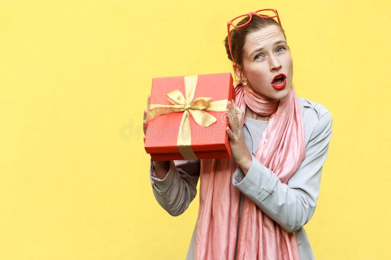 Cant stand, Its my! Playfully young adult girl holding gift box. Isolated on yellow background, studio shot stock image