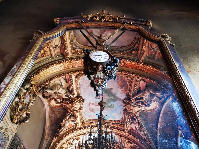 Cantacuzino Palace interior - mirror and old clock. Cantacuzino Palace interior - miroor and old clock. Ceiling reflected in the mirror royalty free stock images