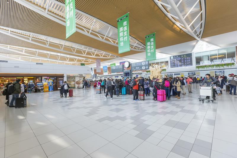 Cantado de turistas en el pasillo de la salida del nuevo aeropuerto de Shin Chitose en Hokkaido, Japón imagen de archivo libre de regalías