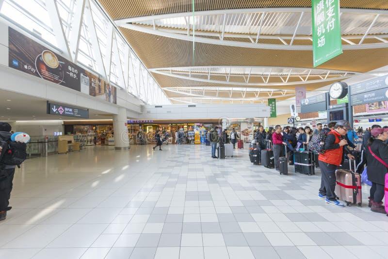 Cantado de turistas en el pasillo de la salida del nuevo aeropuerto de Shin Chitose en Hokkaido, Japón foto de archivo