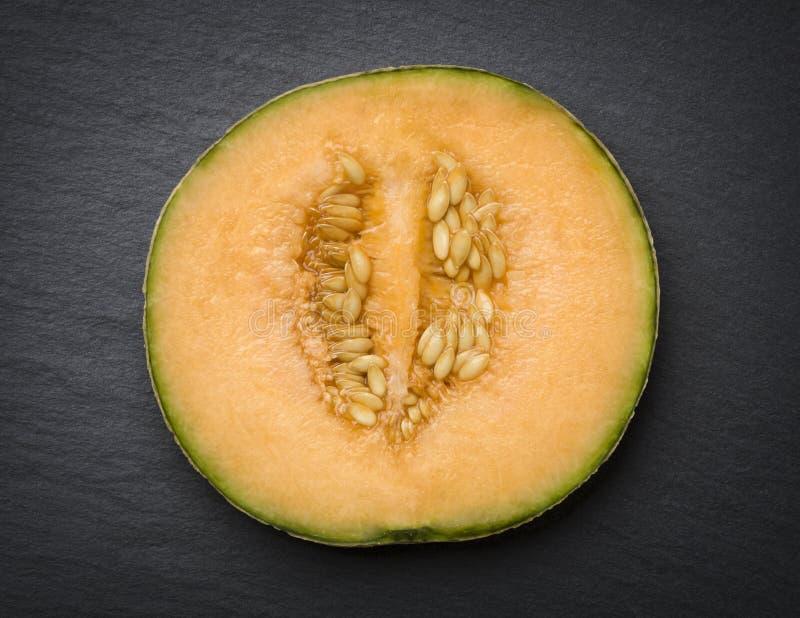 Cantaloup coupé en tranches sur l'ardoise image stock