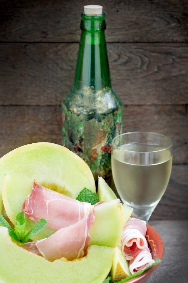 Cantaloup de melon avec le prosciutto et le vin sur la table rustique photo stock