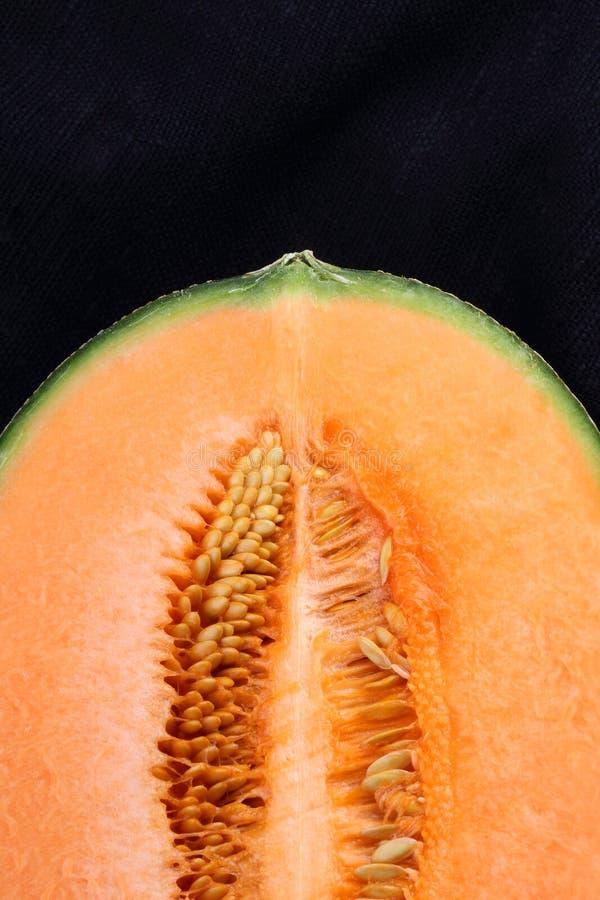 Cantaloup organique sur le tissu noir photographie stock