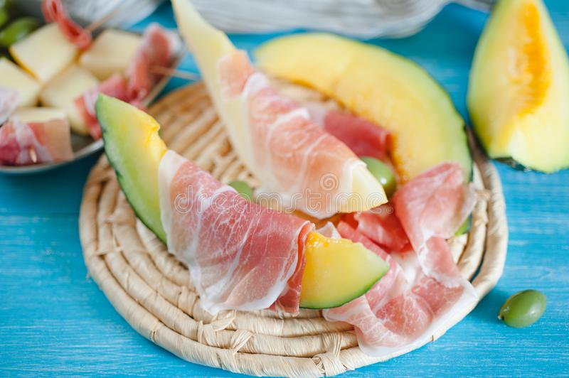Cantaloupe melon, italian ham slices and olives royalty free stock images