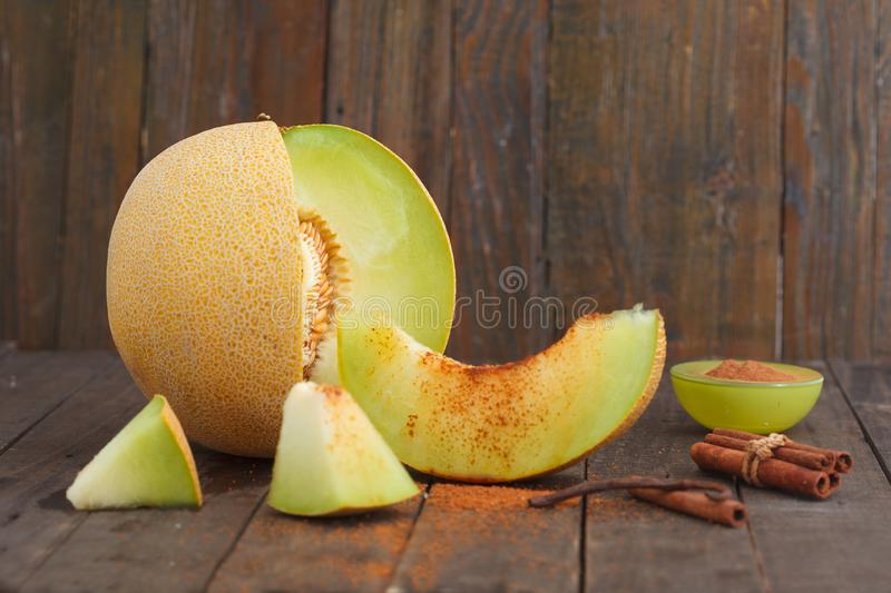 Cantaloupe melon and melon slices with cinnamon and brown sugar on wooden background royalty free stock photography