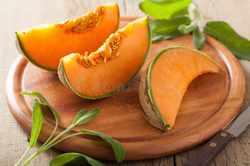 Cantaloupe melon sliced on wooden background royalty free stock images