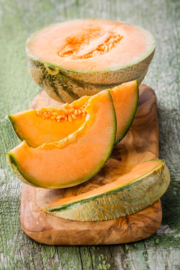Cantaloupe melon. Slices on olive wood cutting board royalty free stock images