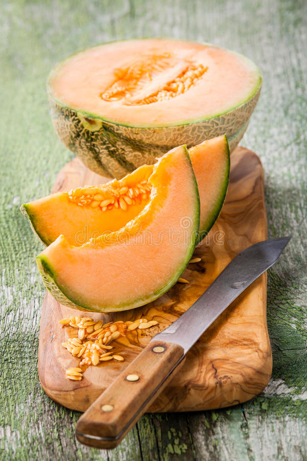 Cantaloupe melon. Slices on olive wood cutting board stock photos