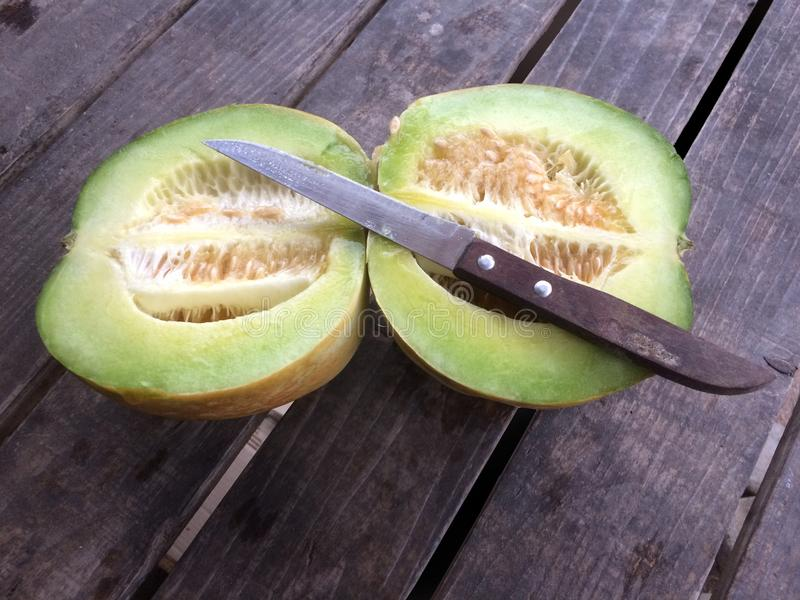 Cantaloupe or muskmelon and knife on old wooden table stock photo