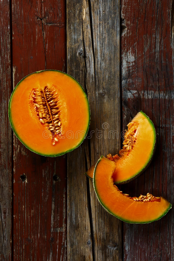 Cantaloupe. Top view of Cantaloupe melon on rustic wooden background. Still life food royalty free stock image