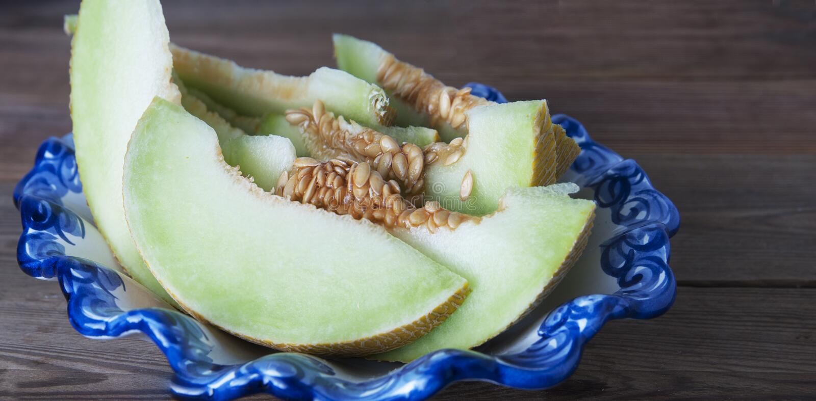 Cantaloupe yellow fresh melon isolated with sliced melon, in beautiful vintage blue plate, wooden table, gray background. Summer f stock photo