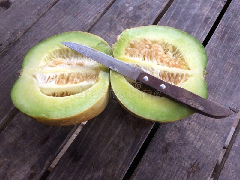 Cantaloupmelon eller muskmelon och kniv på den gamla trätabellen arkivfoto