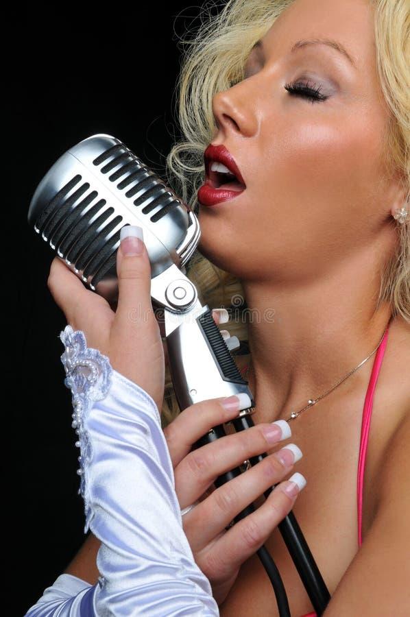 Cantante biondo sul microfono fotografie stock