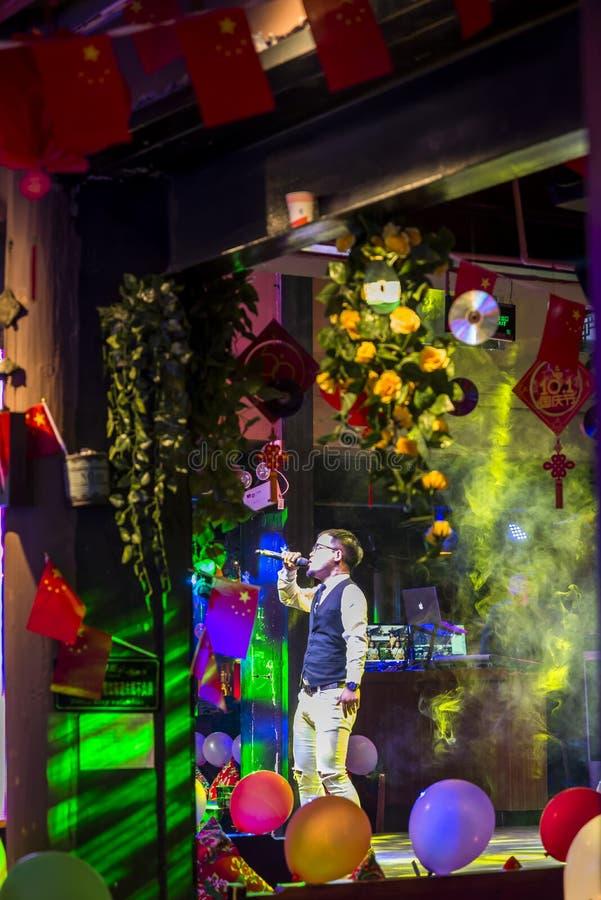 Cantante che canta in una barra colourfully decorata, Dali, Cina immagine stock