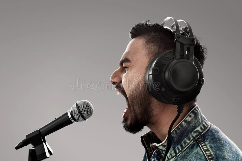 Cantante che registra una canzone su fondo grigio fotografia stock