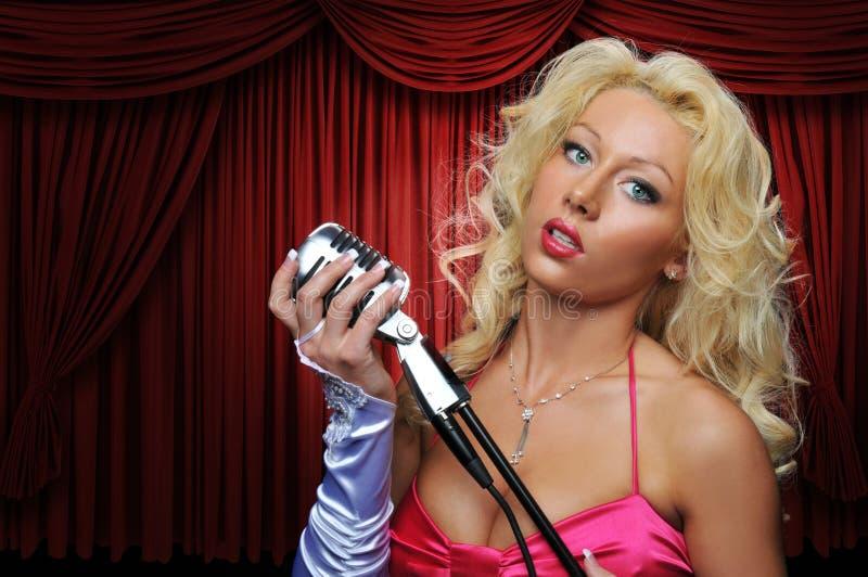 Cantante con el micrófono de la vendimia en etapa fotografía de archivo libre de regalías