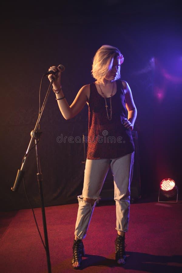 Cantante confiado que sostiene el micrófono en club nocturno iluminado fotografía de archivo libre de regalías
