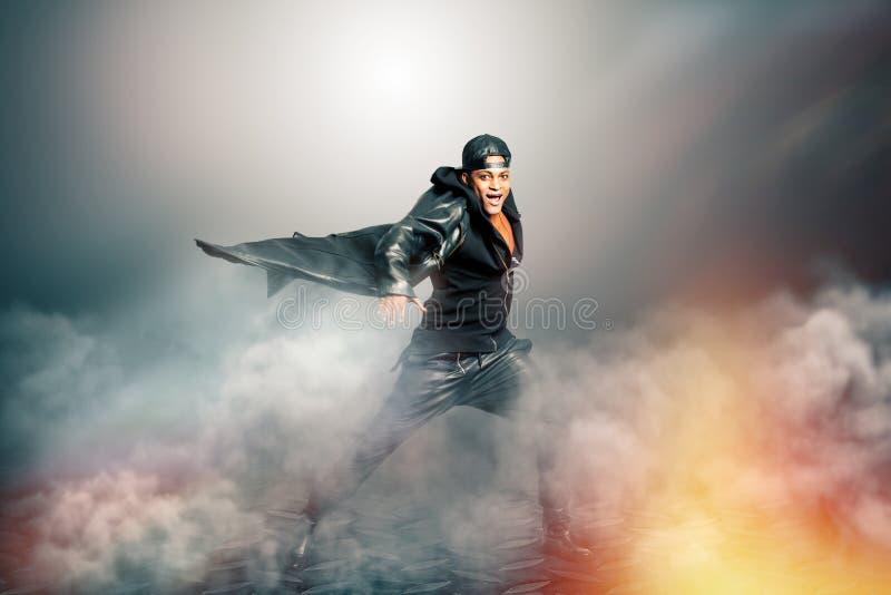 Cantante de roca de sexo masculino con el cabo en paisaje misterioso con humo fotografía de archivo