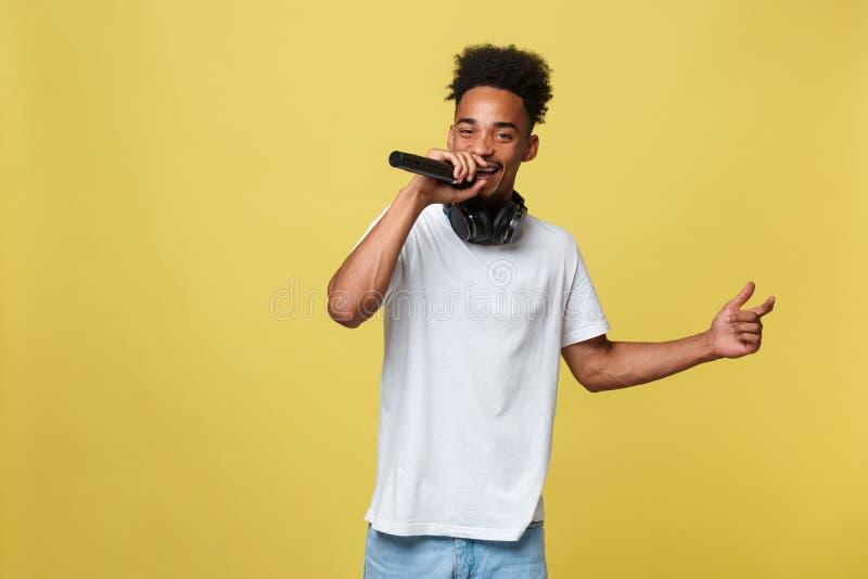 Cantante de sexo masculino afroamericano hermoso joven Performing con el micrófono Aislado sobre fondo del oro amarillo fotografía de archivo