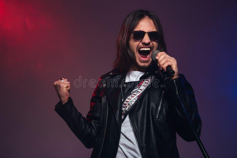 Cantante de sexo masculino joven atractivo con el pelo largo que canta usando el micrófono foto de archivo