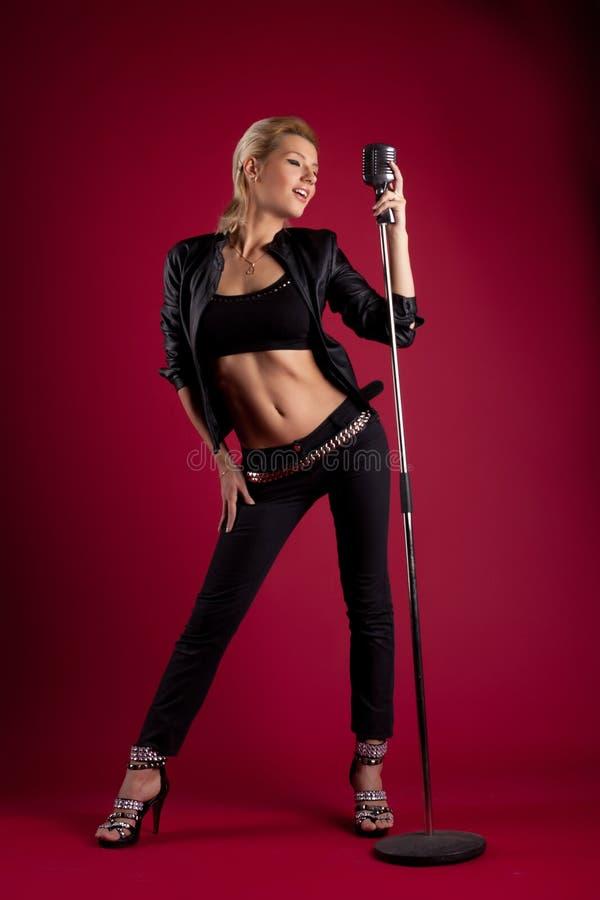 Cantante di bellezza in cuoio nero su colore rosso con il mic fotografie stock