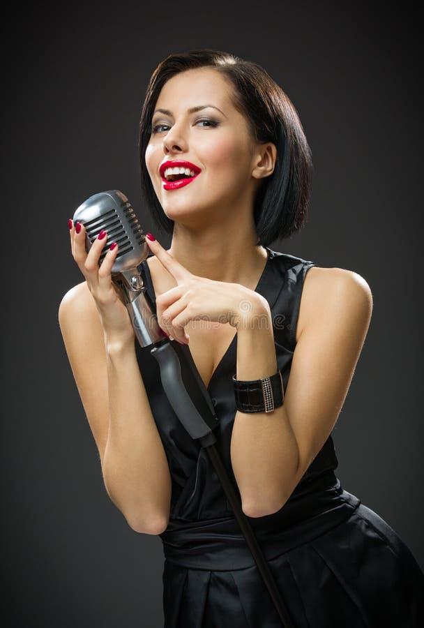Cantante femminile che tiene microfono fotografia stock libera da diritti