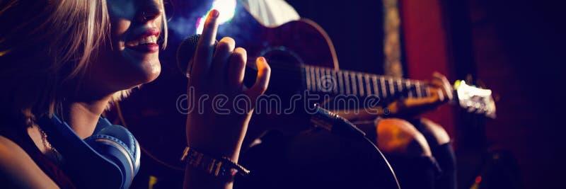 Cantante femminile con il chitarrista in scena fotografie stock