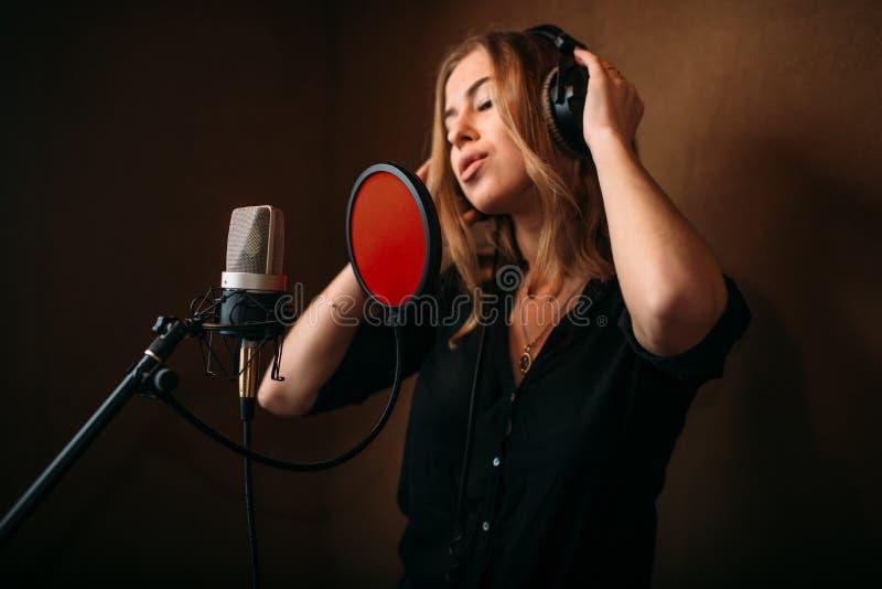 Cantante femminile in cuffie contro il microfono fotografie stock