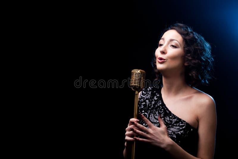 Cantante hermoso de la muchacha que canta la canción emocional con micropho retro imágenes de archivo libres de regalías