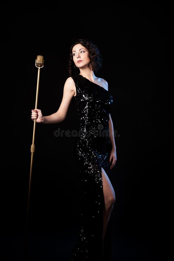 Cantante hermoso de la muchacha que sostiene el micrófono de oro del vintage imagenes de archivo