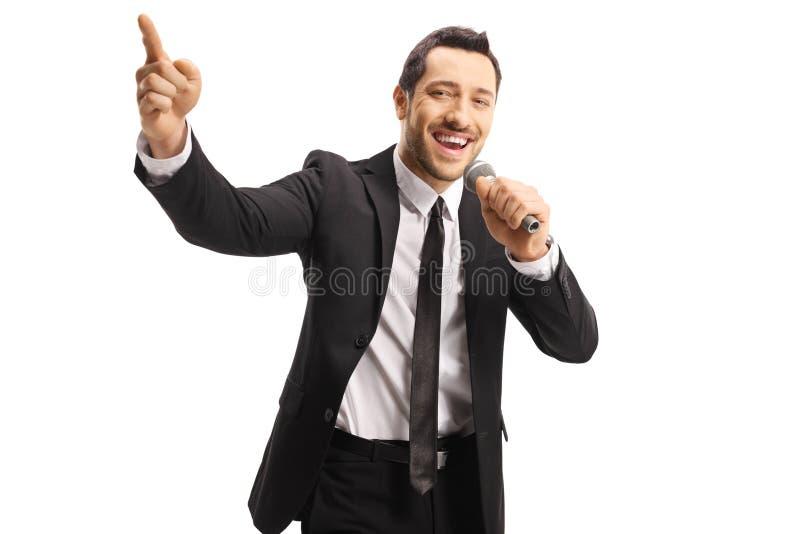 Cantante maschio bello con un microfono che indica su fotografie stock