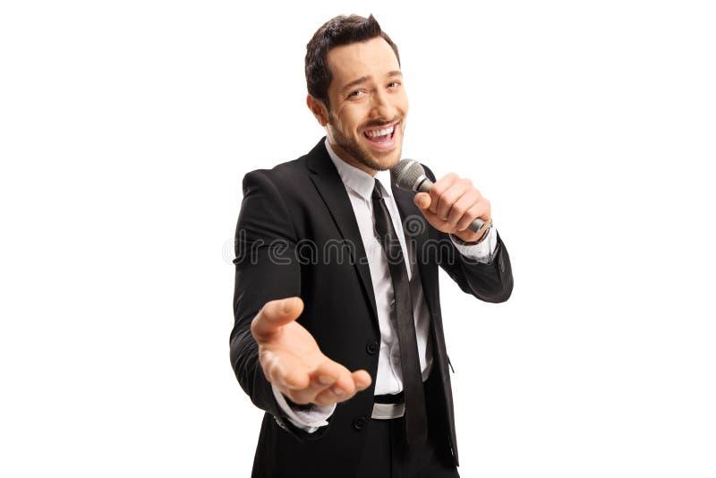 Cantante maschio bello in un vestito nero che canta su un microfono fotografia stock libera da diritti