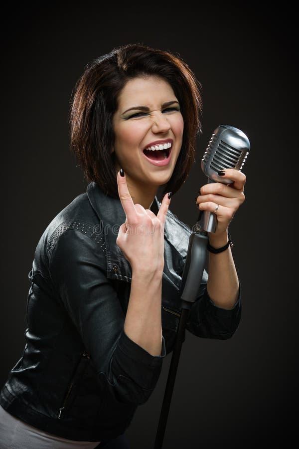Cantante rock femminile che tiene mic fotografia stock libera da diritti