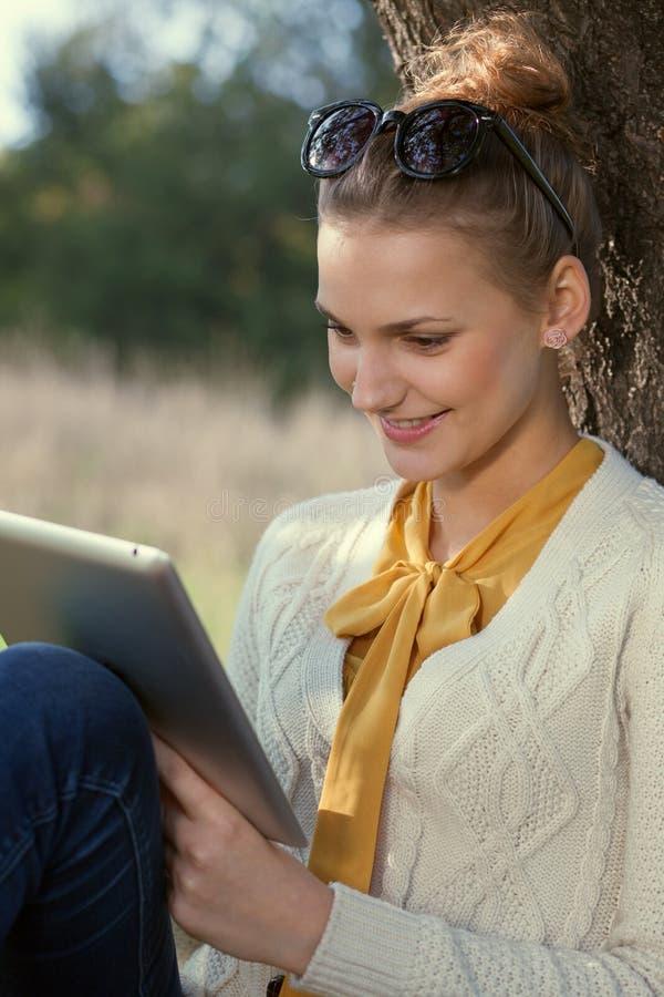 Cante a jovem mulher do ipad no parque fotos de stock royalty free