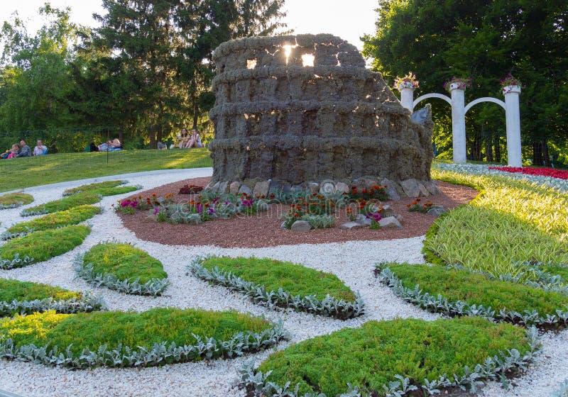 Canteiro de flores e escultura bonitos de um Colosseum parcialmente destruído nele fotografia de stock