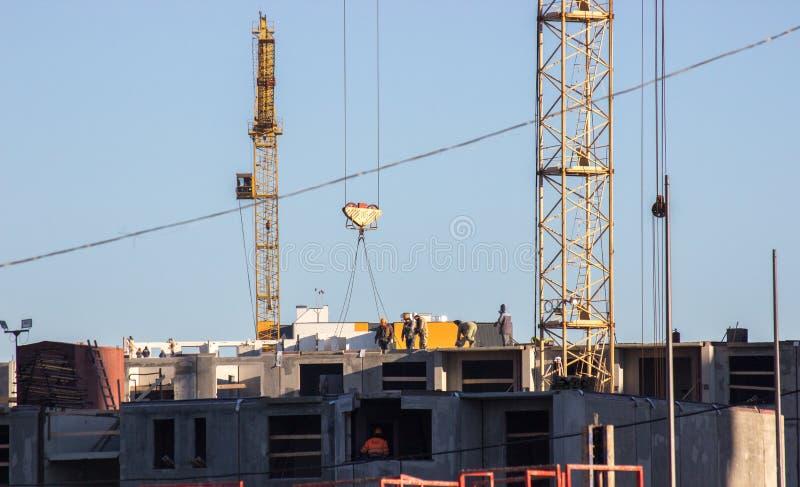 Canteiro de obras com guindaste Diversos guindastes estão funcionando no complexo da construção contra o céu azul um grupo de con fotos de stock