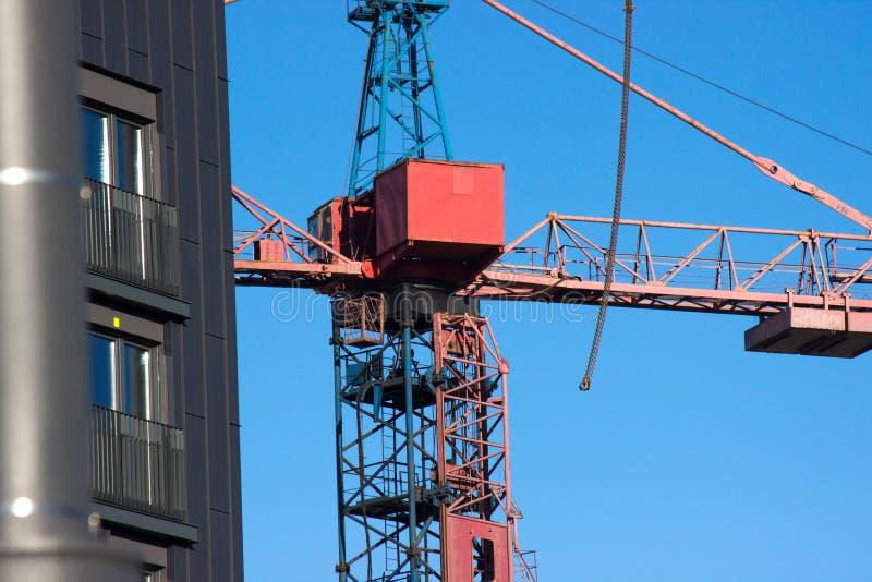 Canteiro de obras com o guindaste vermelho no fundo do céu azul e na casa cinzenta A construção, obras, levantar pesado carrega a fotografia de stock