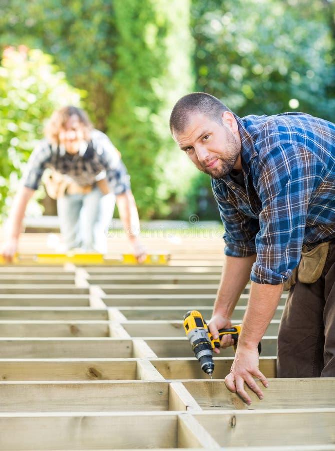 Canteiro de obras de Holding Drill At do carpinteiro fotografia de stock