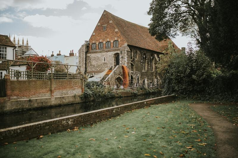 Beautiful church and river in Canterbury, United Kingdom. CANTERBURY, ENGLAND - October 28th, 2018: A nice old church, between generic architecture, close to the royalty free stock photo