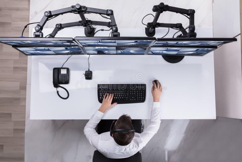 Cantidad de Monitoring Multiple Camera del guardia de seguridad en el ordenador fotografía de archivo