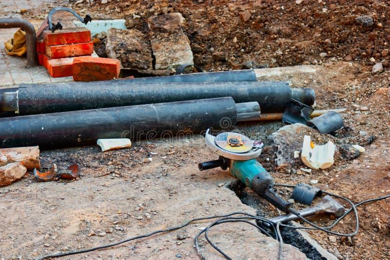 Cantiere con la smerigliatrice dell'azionamento di angolo che si trova nella sporcizia e nel mazzo di waterpipes fotografie stock libere da diritti