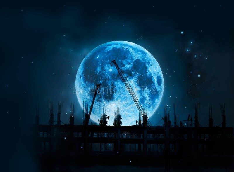 Cantiere con le gru e la luna blu piena dei lavoratori alla notte fotografia stock libera da diritti